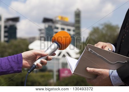 Press interview with microphone held in front of businessman or politician