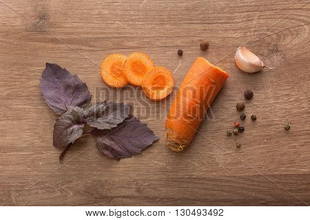 Top view of sliced carrot clove of garlic branch of purple basil and black pepper on the wooden table
