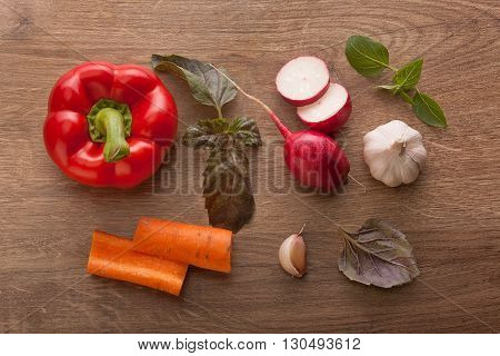 Top view of red paprika sliced radish two pieces of carrot garlic and leaves of basil on the wooden table