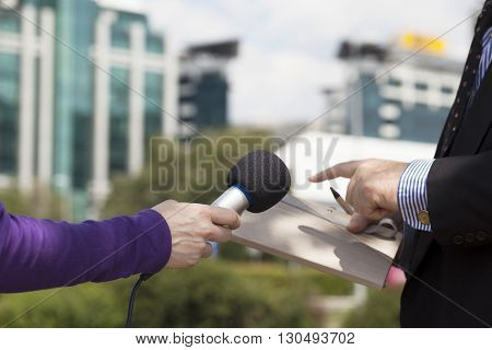 Interview with microphone held in front of businessman, spokesman or politician