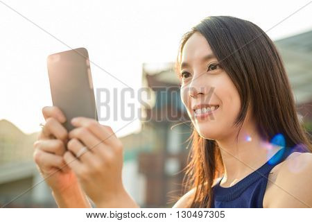 Woman using cellphone at outdoor under sunset