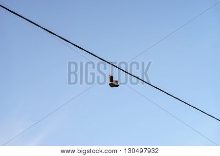 Old pair of shoes hanging on telephone wire against blue sky life change concept