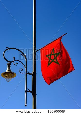 Sunlit Moroccam flag fixed to a lamp post.
