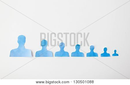 business, employment, population, career and hiring concept - close up of paper people shapes on white board