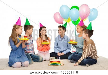 childhood, holidays, celebration, friendship and people concept - happy smiling children in party hats with birthday cake and balloons