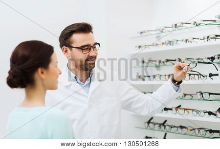 health care, people, eyesight and vision concept - optician choosing glasses for woman at optics store