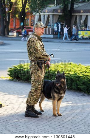 Zaporizhia/Ukraine- May 19, 2016: Dog handler, explosives expert  in uniform with dog guarding public safety during  celebration of traditional Ukrainian embroidered clothes, known as vyshyvanka  day, celebrated in all regions of Ukraine