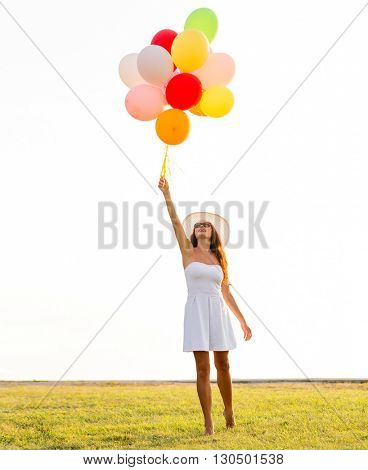 happiness, summer, holidays and people concept - smiling young woman wearing sunglasses with balloons outdoors