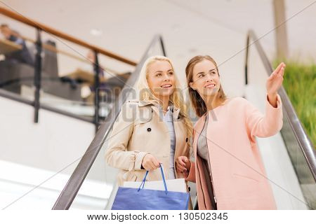 sale, consumerism and people concept - happy young women pointing finger on escalator in mall
