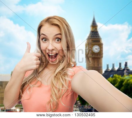 travel, tourism, emotions, expressions and people concept - happy smiling young woman taking selfie and showing thumbs up over big ben london and city background