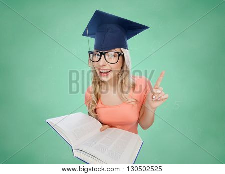 people, education, knowledge and graduation concept - smiling young student woman in mortarboard and eyeglasses with encyclopedia book pointing finger up over green school chalk board background