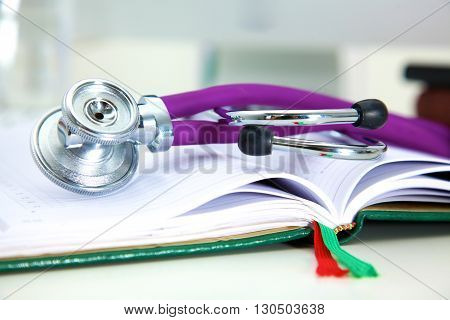 Stethoscope lying on a notebook computer in the background and books.