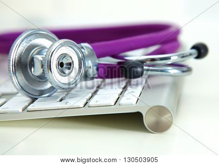 Silver stethoscope lying down on an laptop, toned blue.