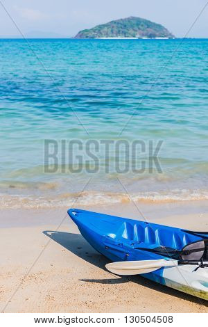 The emty blue kayak on the beach ready for paddler.