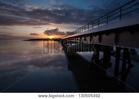 Sunset over the railway bridge going from Swansea to Llanelli crossing over the Loughor estuary, South Wales.