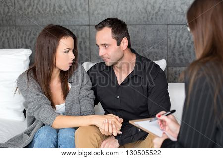 Young woman and man on couple therapy indoor. Holding each other hands. Looking into each other