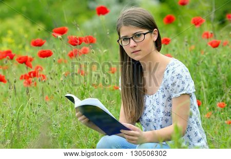 Teen girl reading book in the poppies field