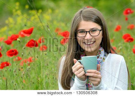 Teen girl drink cup of tea on poppy field