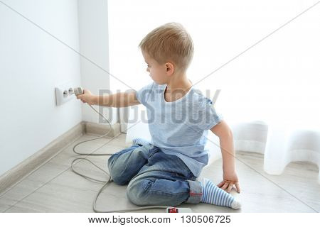 Little baby playing with plug