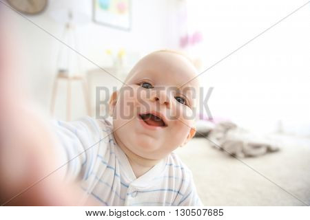 Adorable baby boy reaching to a camera, close up