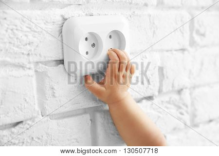 Little baby playing with socket on the wall