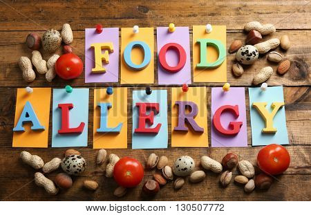 Sign FOOD ALLERGY with nuts on wooden background