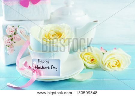 Happy Mother's day concept. Tableware and roses on a wooden table