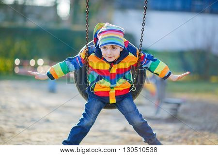 Adorable kid boy having fun with chain swing on outdoor playground. child swinging on warm sunny spring or autumn day. Active leisure with kids. Boy wearing colorful clothes