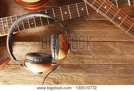 Guitars and headphones on wooden background