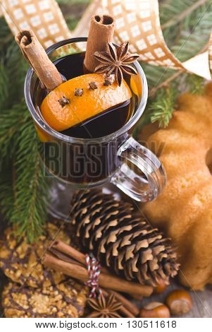 Hot spiced mulled wine with orange garnish on a wooden background