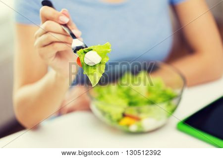healthy eating, diet, food and people concept - close up of young woman eating vegetable salad with fork at home