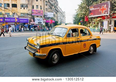 KOLKATA, INDIA - JAN 17, 2013: Yellow Ambassador taxi car goes through the indian street on January 17, 2013 in Kolkata India. First Ambassador was produced by the Yellow Cab Manufacturing Company in 1921