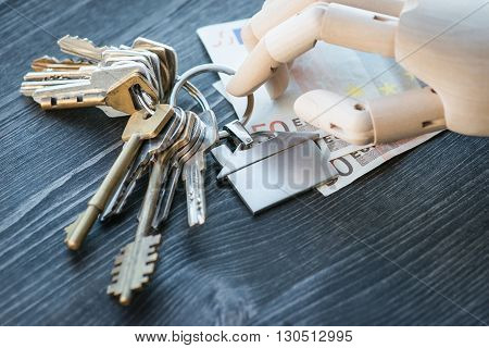 Artificial Wooden Hand Holding The Keys And Money, On A Wooden Table
