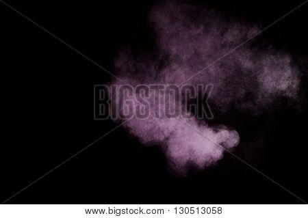 Purple powder explosion on black background. Colored powder cloud. Colorful dust explode. Paint Holi.