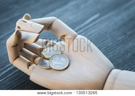 Artificial Wooden Hand Holding The Money, On A Wooden Table