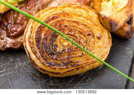 Grilled sliced onion on grill metal pan as a garnish for mexican beef steak. Macro. Photo can be used as a whole background.