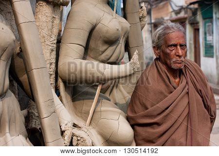 KOLKATA, INDIA - JAN 15, 2013: Senior asian man stands near the woman sculpture at Kumartuli artistic area on January 15, 2013 in India. Populat. of Kolkata is 4.5 million out 25 million are males