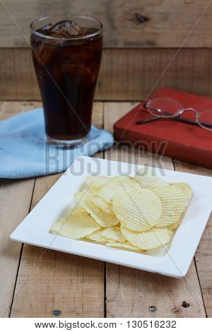 Potato chips and soft drink in glass on wood background Selection focus