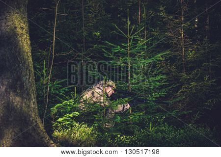 Hiding Poacher with Rifle in Deep Spruce Forest. Hunting Poacher. Poaching Theme.