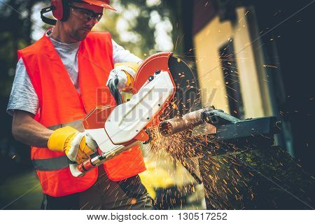 Men Using Mobile Electric Metal Cutter. Pipe Cut. Construction Theme.