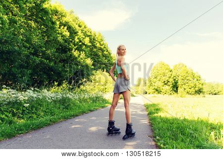 fitness, sport, summer and healthy lifestyle concept - happy young woman in rollerskates riding outdoors