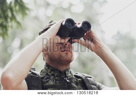 hunting, war, army and people concept - young soldier, ranger or hunter with binocular observing forest