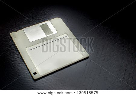 grey floppy disk dark black wood background  vintage technology