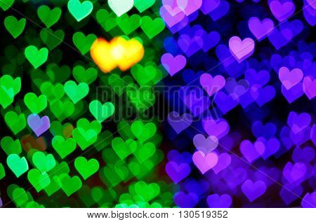 Blurring lights bokeh background of green and blue hearts