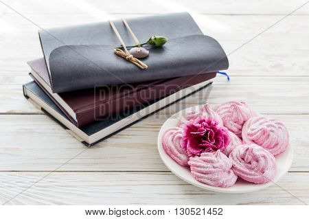 Homemade marshmallow dessert with carnations and notebooks
