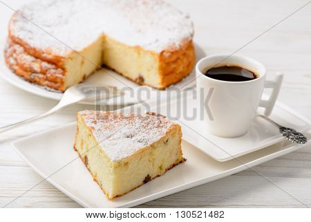 Cheesecake slice and cup of coffee on wooden background .