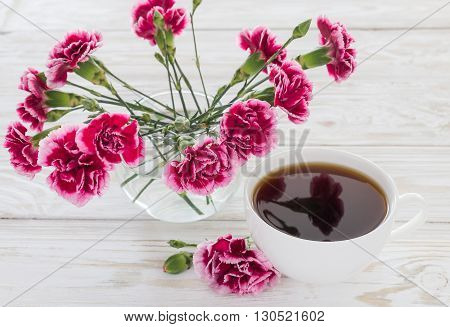 Cup of coffee and pink carnations on wooden table