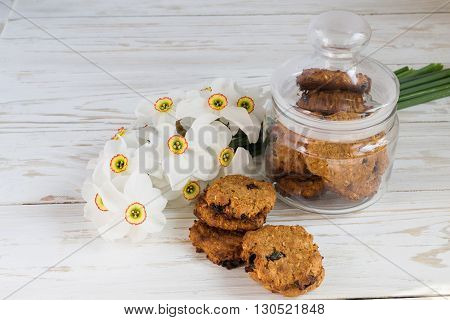 Freshly baked oatmeal raisin cookies in clay bowl and narcissus on rustic wood background