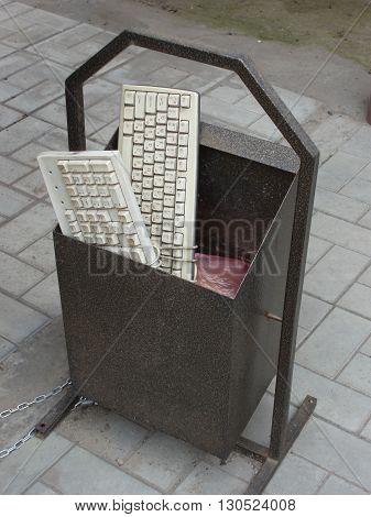 Two old broken keyboard in the dustbin on the street.