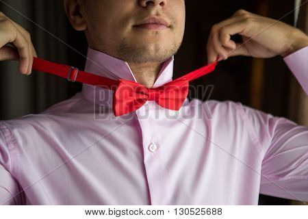 Stylish and handsome groom tying his bow-tie in the morning of the wedding day.